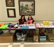 Project Rise interns Sara Sutorius (Left) and Cassandra Milham (Right) pass out giveaways to the families